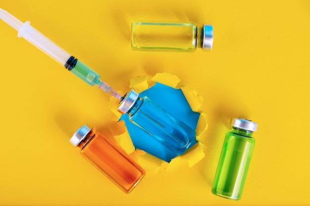 Медицинские ампулы и шприц на желтом фоне. скопируйте пространство. выборочный фокус