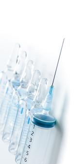 白い背景の上の医療アンプルと注射器