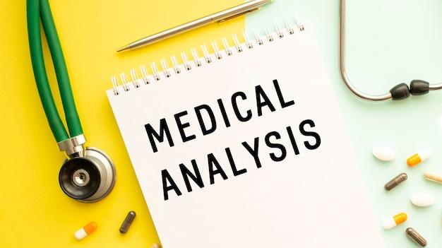 의료 분석은 약과 청진기 옆의 색상 표에 노트북에 기록됩니다.