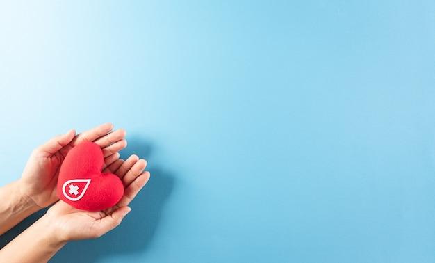 Медицинские и донорские концепции рука держит красное сердце ручной работы со знаком или символом донорства крови на всемирный день донора крови