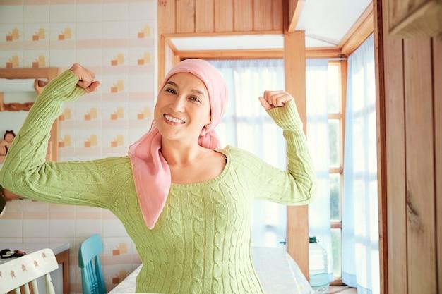 의료 및 건강 개념. 암을 앓고있는 여성이 집에서 생존자가 된 것에 대해 힘과 힘의 몸짓을하고 있습니다. 그녀는 분홍색 스카프와 녹색 스웨터를 입습니다.