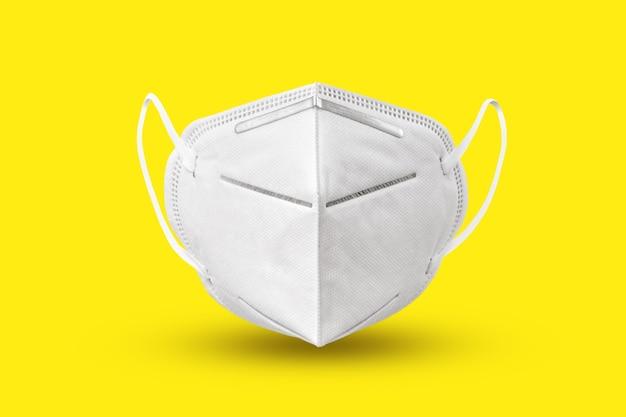 Медицинская антибактериальная защитная маска для лица, плавающая над желтым фоном с мягкими тенями, копией пространства. концепция профилактики респираторных заболеваний и вирусов.