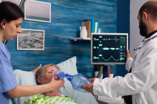 病気の入院中の年配の女性がアンブバッグで呼吸するのを助ける医療助手
