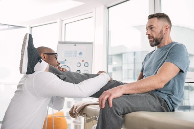 Medical assistance. professional smart doctor holding his patients leg while providing medical assistance