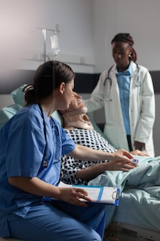 Medical assistant checking oximeter attached to senior man laying in hospital bed, monitoring pacient and african doctor discussing with sick hospitalized senior man.