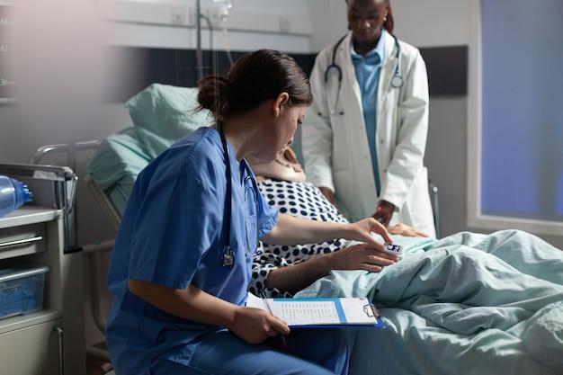 病院のベッドに横たわっている年配の男性に取り付けられた酸素濃度計をチェックし、病気の入院中の年配の男性と話し合っている患者とアフリカの医師を監視している医療助手。