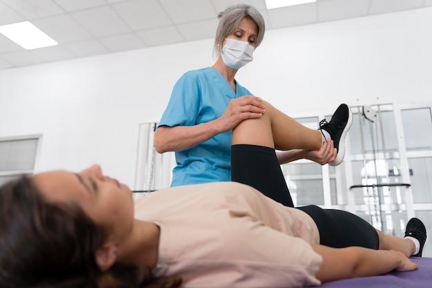 물리 치료 운동으로 환자를 돕는 의료 조수