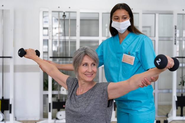 Medical assistant helping patient with physiotherapy exercises