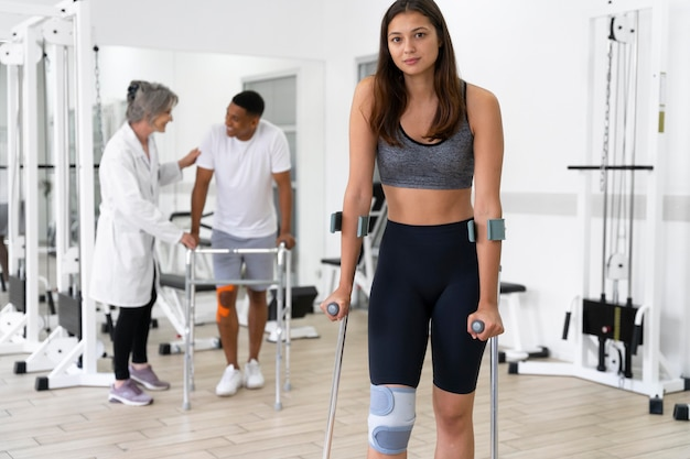 Medical assistant helping patients with physiotherapy exercises