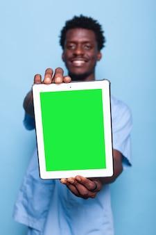 수직 녹색 화면이 있는 디지털 태블릿을 들고 있는 의료 보조