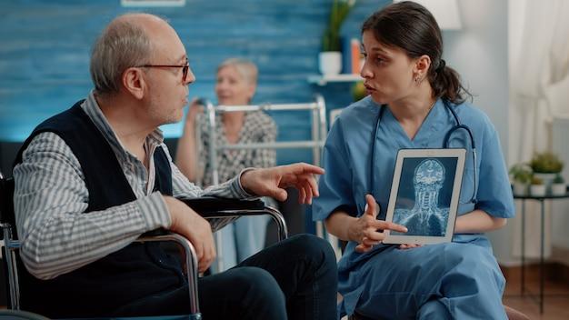 健康診断のためのx線スキャンでタブレットを保持している医療助手