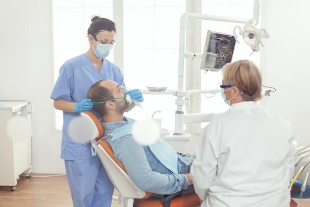 歯科手術のために病人患者を検査する酸素マスクを置く医療助手
