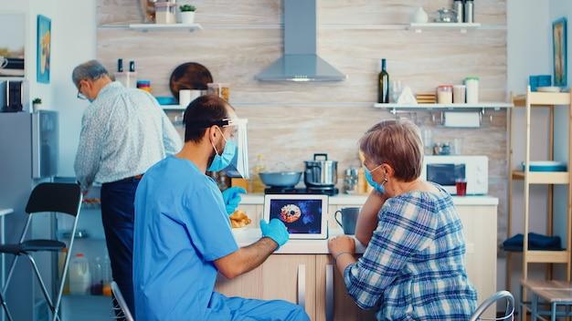 家庭訪問中に年配の女性とコロナウイルスのパンデミックについて話している医療助手。老夫婦の男性看護師ソーシャルワーカーがcovid-19の広がりを説明し、リスクグループの人々を助ける
