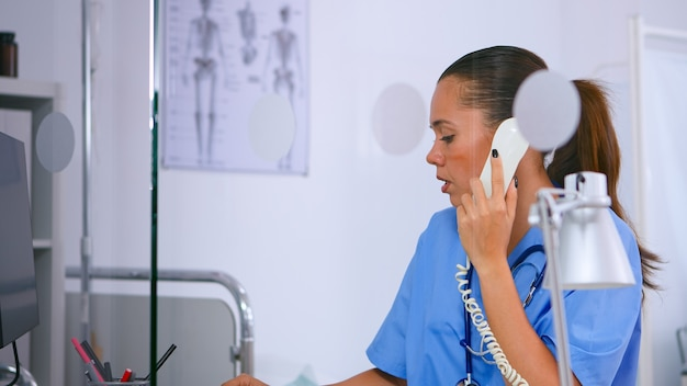 Medical assistant talking at phone and typing on computer offering consultation in hospital clinic. woman receptionist in medicine uniform, doctor nurse assistant helping with telehealth communication
