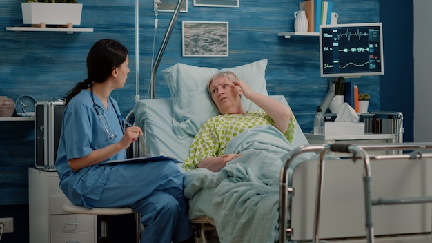 Medical assistant talking to senior patient with disease in bed