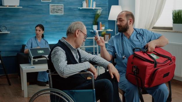 症状検査に体温計を使用する医療助手