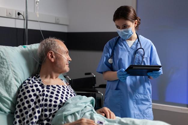 Assistente medico con maschera di protezione che controlla il trattamento dell'uomo anziano che legge le note sul tablet pc