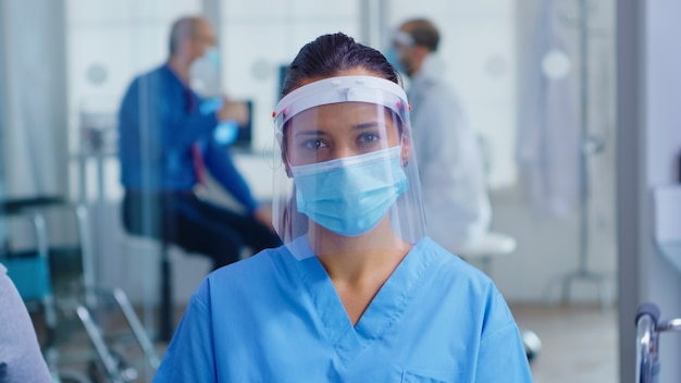 병원 대기실에서 카메라를 보고 있는 코로나바이러스에 대비한 바이저와 얼굴 마스크를 갖춘 의료 보조. 검사실에서 의사 컨설팅 수석 남자입니다.