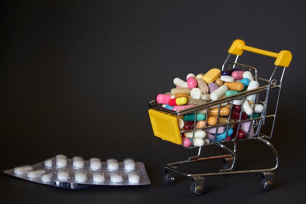 Medical background or concept. close-up of a shopping trolley filled with colorful pills. cart from the supermarket with different medicines and tablet blister