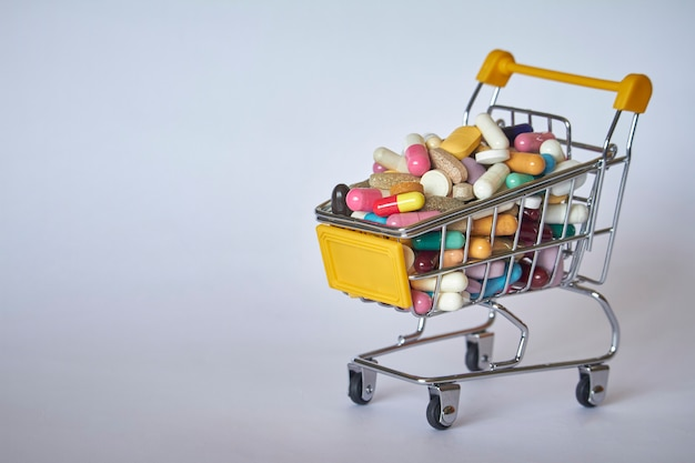 Medical background or concept. close-up of a shopping trolley filled with colorful pills. cart from the supermarket with different medicines.