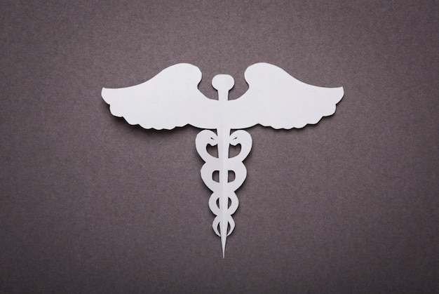Medical background, paper cut of caduceus medical symbol with co
