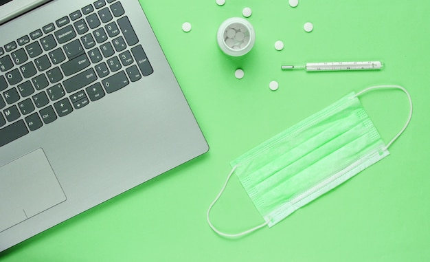 의료 배경. 현대 의사의 작업 영역. 노트북, 알약, 얼굴 마스크, 녹색 배경에 온도계. 평면도. 플랫 레이