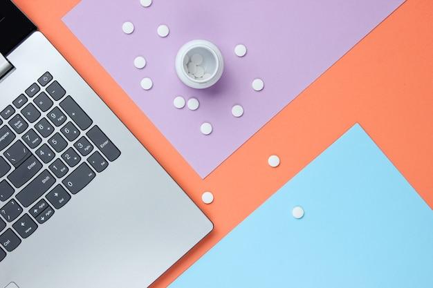 医学的背景。現代の医者のワークスペース。ラップトップ、色付きのパステルカラーの背景に丸薬。上面図。