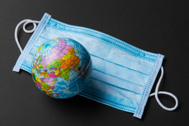 On a medical bandage lies a mock planet earth, the concept of a global pandemic of the coronavirus