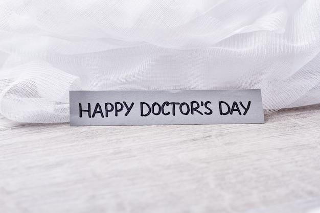 흰색 바탕에 의료 붕대입니다. 의사의 날을 축하합니다.