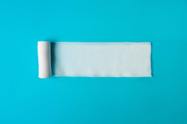 Медицинская повязка раскручивается на голубом. здоровье. здоровый образ жизни . понятие фармакологии. концепция лекарств. концепция медицинских инструментов. концепция медицины.