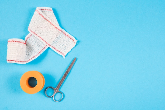 Medical bandage with scissors and sticking plaster on blue background