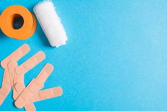 Medical bandage with sticking plaster and cotton gauze bandage on blue background