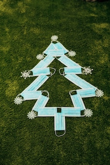 Medical blue masks made christmas tree on a green background