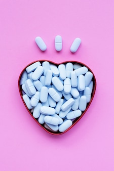 Medical blue pills with heart shaped box on pink surface.
