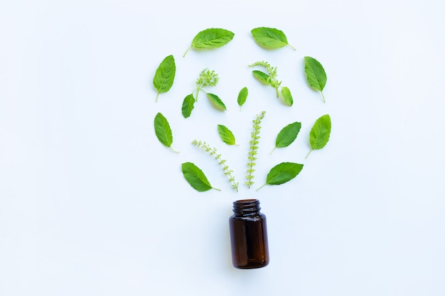 Medical bottle glass with green holy basil leaves and flower on white