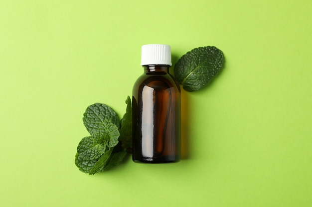 Medical bottle and mint on green, space for text
