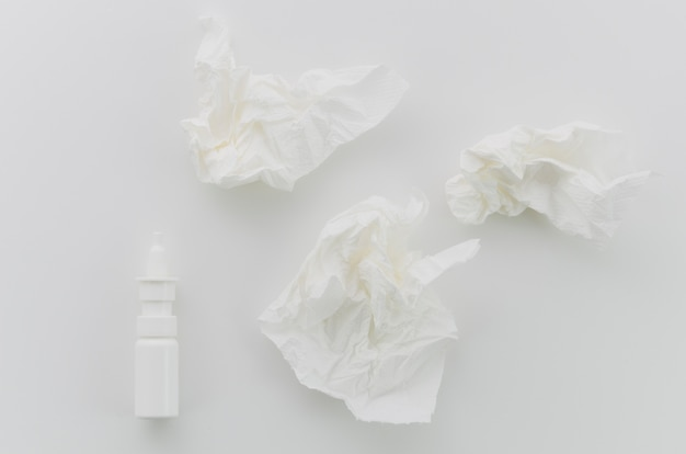 Medical bottle with crumpled paper on white background
