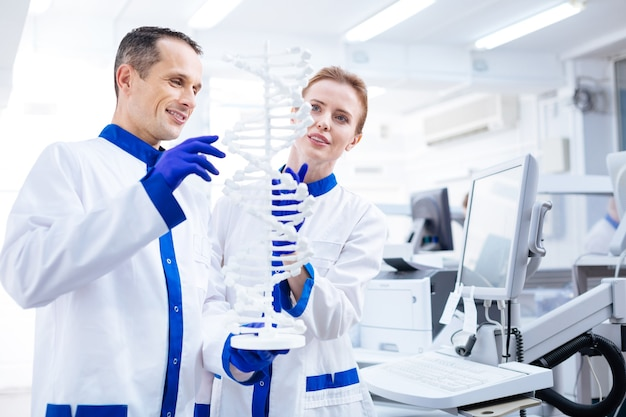 의료 브레인 스토밍. 모델을 잡고 실험실에 서있는 동안 분자 구조에서 연구하는 매력적인 잠겨있는 남성 및 여성 과학자