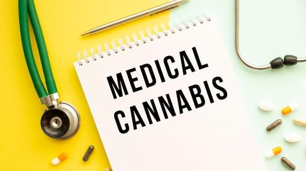 의료용 cannabis는 알약과 청진기 옆의 색상 표에 노트북에 기록되어 있습니다.