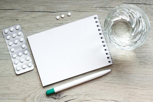 Таблетки медицинские капсулы, стакан воды, ручка, лист бумаги для заметок на деревянном фоне. понятие здоровья, назначение