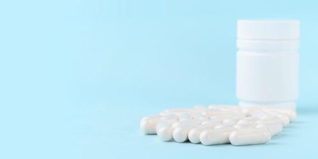Medical capsules of glucosamine chondroitin, amino acids, maltodextrin on blue surface