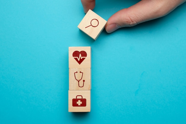 Medical care search concept with icons on wooden blocks.