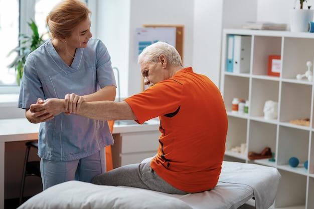 의료 센터. 그의 손을 잡고 그녀의 환자 앞에 서 기쁘게 친절한 간호사
