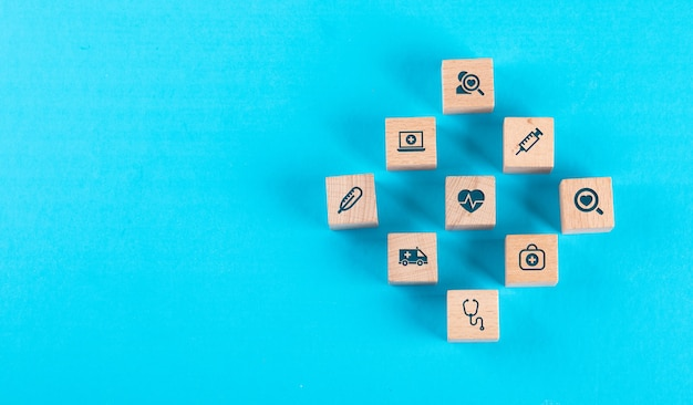 Medical check up concept with wooden blocks with icons on blue table flat lay.