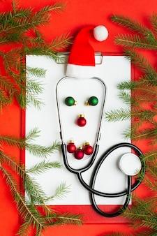클립보드에 청진기와 공의 재미있는 얼굴을 가진 의료 크리스마스 개념