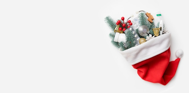 Medical christmas flat lay banner with santa hat and a stethoscope, pills, thermometer and new year's decor in it on white background with copy space.
