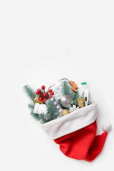 Medical christmas flat lay with santa hat and a stethoscope, pills, thermometer and new year's decor in it on white background with copy space.