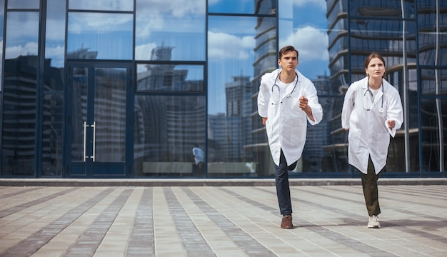 Коллеги-медики бегут по городской улице в службу экстренной помощи. фото с копировальным пространством.