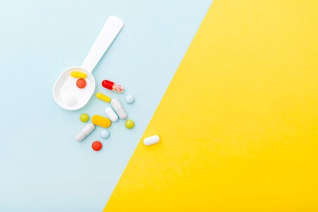 Медицинский состав с таблетками цвета, наркотиками, видом сверху. набор капсул, лекарств. место для текста.