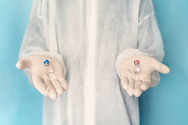 Medical concept. the choice of medication by analogy with the matrix. choosing the best vaccine. a doctor in a white lab coat and protective gloves holds a blue and red ampoule in his hands.